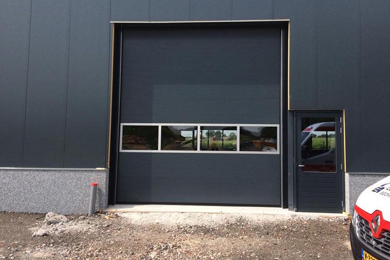 bedrijfsdeuren specialist, sectionaaldeur met rechts een loopdeur